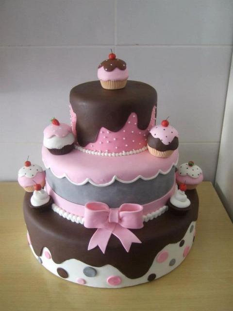 Bolo de três andares com decoração de cupcakes nas cores rosa e marrom