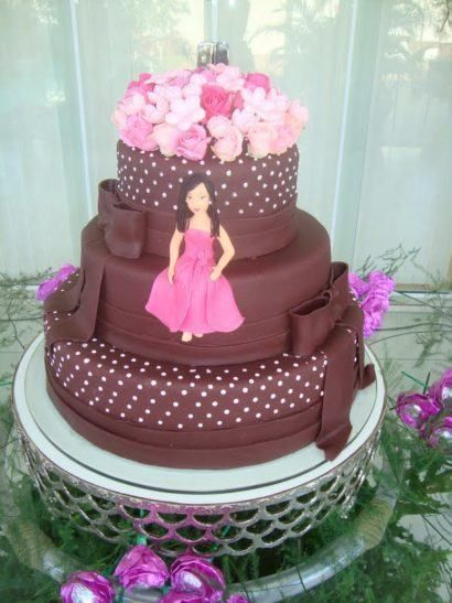 Bolo com três andares na cor marrom com decoração em rosa