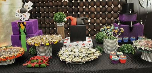 Mesa de doces decorada com chapéu da Arlequina e roupa do Coringa