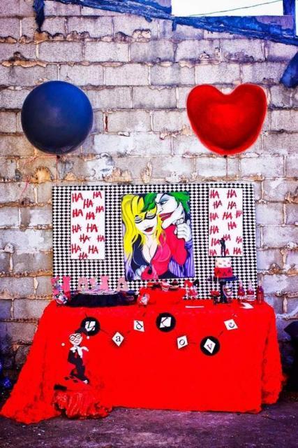 Mesa com decoração em vermelho e roxo com tema Arlequina e Coringa