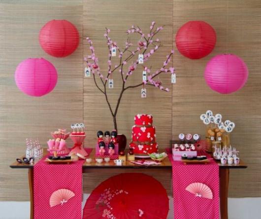 mesa de festa japonesa decorada em vermelho e rosa com balões