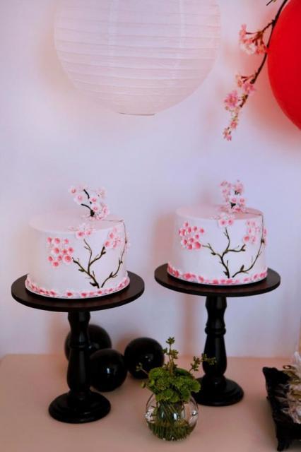dois bolos brancos decorados com flores de cerejeiras rosas