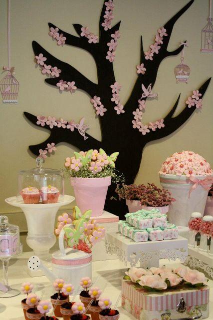 mesa decorada de festa japonesa com desenho de cerejeira atrás