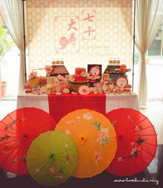 mesa decorada de doces em festa japonesa com tecido com dizeres japoneses ao fundo