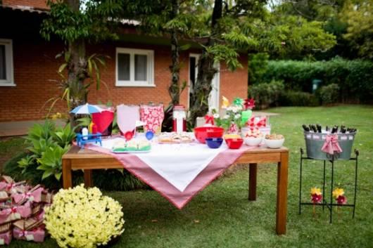 mesa de madeira com toalha de xadrez vermelha e branca em festa piquenique