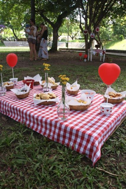 mesa com toalha de xadrez vermelho e branco em festa piquenique