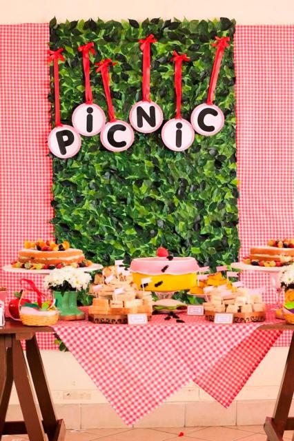 mesa com decoração em vermelho e painel de grama falsa para festa piquenique
