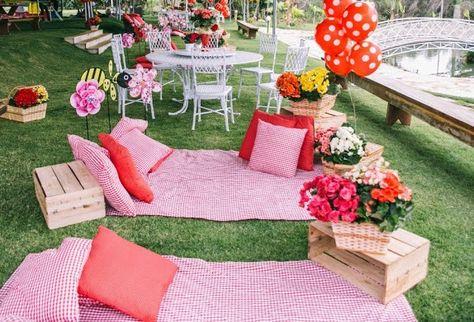 toalhas rosa e almofadas no chão em festa piquenique