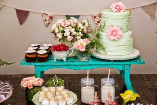 mesa azul com flores e doces para festa piquenique