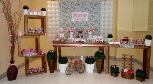 mesa decorada em rosa de festa de 80 anos com painel florido ao fundo
