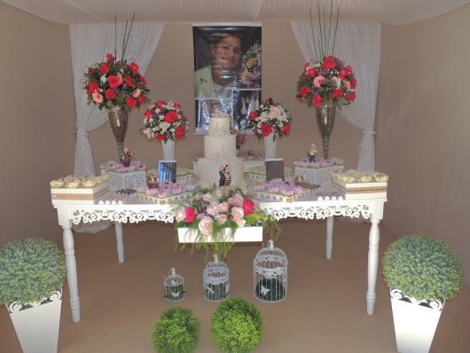 mesa decorada de festa de 80 anos com painel com foto ao fundo