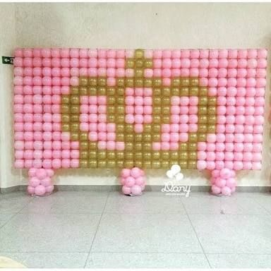 parede de balões com desenho de coroa