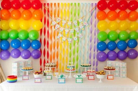 parede de balões com fitas coloridas no meio
