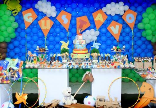 parede de balões com cenário de árvores e nuvens