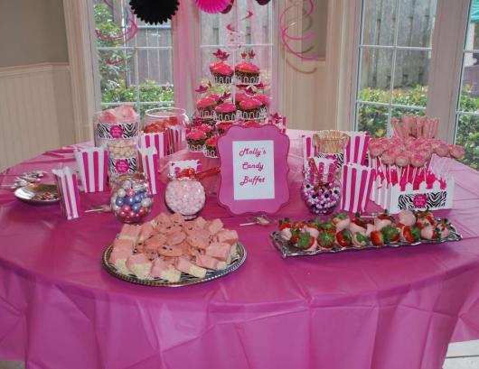 Mesa decorada com embalagens, doces e cup cakes cor de rosa.