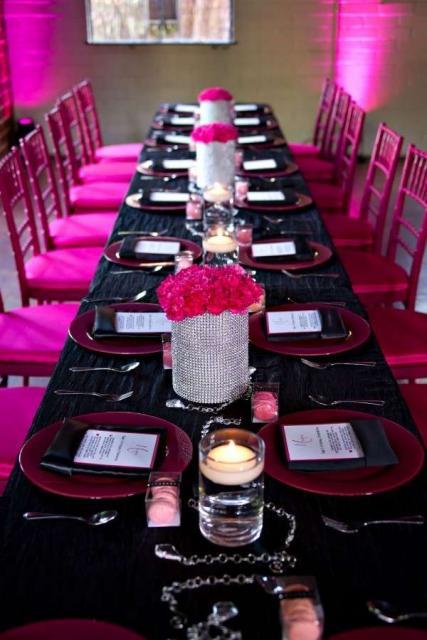 Mesa preta e cadeiras rosas.
