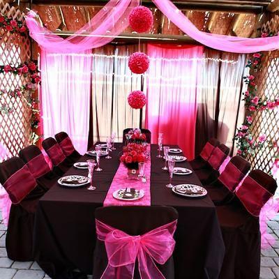 Mesa com toalha marrom escura e flores decorativas,