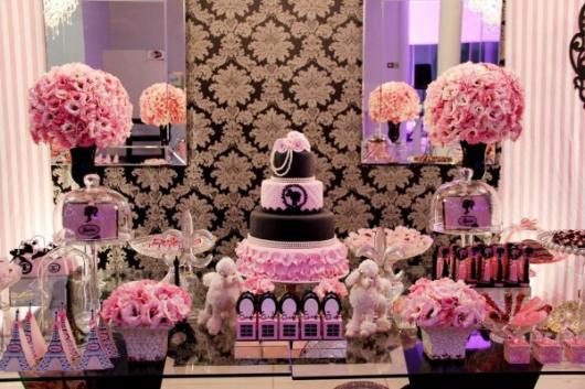 Mesa decorada na cor rosa com flores e espelhos.