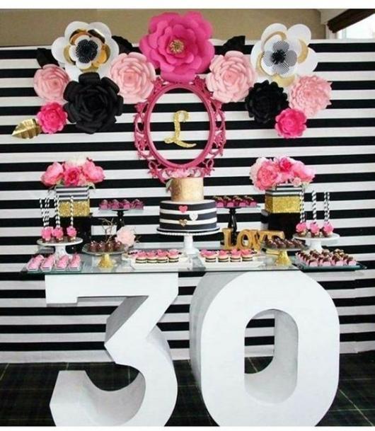 Festa de 30 anos com mesa de vidro e flores decorativas.