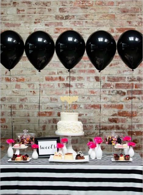Balões pretos amarrados na mesa.