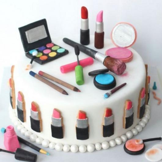 Bolo com o tema maquiagem, decorado com vários itens de beleza.