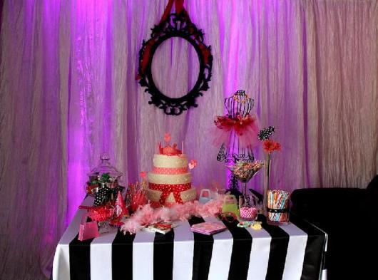 Mesa decorada com detalhes cor de rosa e toalha em preto e branco.