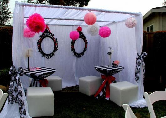 Ambiente decorado com cortinas brancas, balões cor de rosa e molduras de espelho pretas.