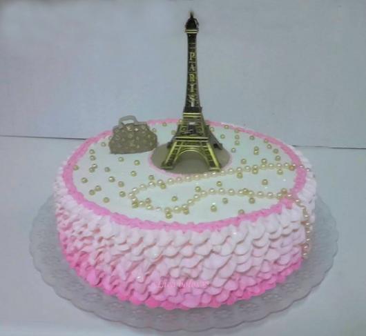 bolo com chantilly ao redor e Torre Eiffel no topo com pérolas