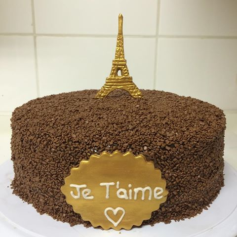 bolo de chocolate com torre eiffel dourada no topo