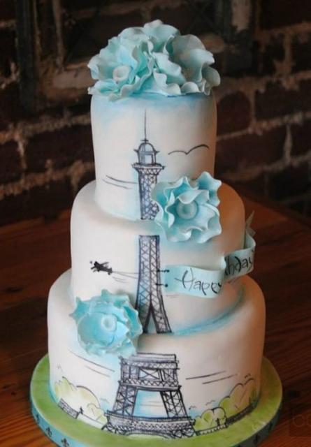 bolo branco com detalhes em azul e torre Eiffel desenhada