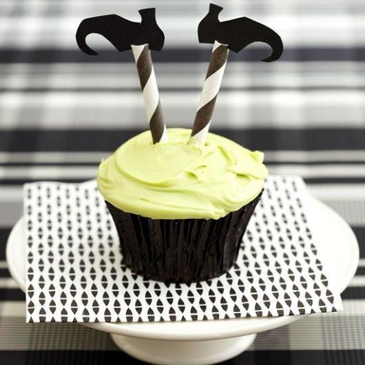 Cupcake com dois palitos com sapatinhos, imitando as pernas de uma bruxa.