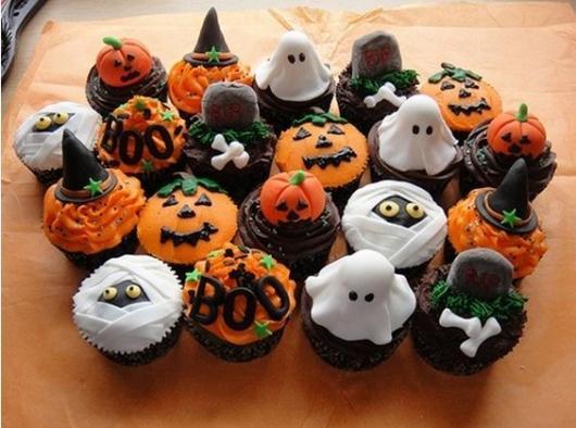 Cupcakes decorados com abóboras, fantasmas e chapéus de bruxa.