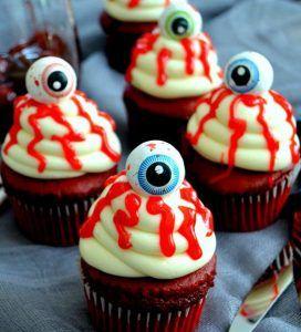 Cupcakes com olhos e calda de morango em cima.
