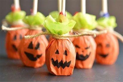 Pirulitos embrulhados em papél que imita uma abóbora de Halloween.