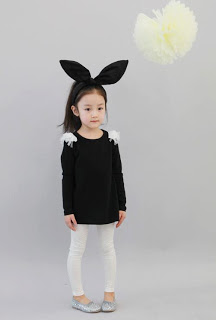 menina com blusa preta, legging branca e orelhas de coelho como fantasia de Halloween infantil improvisada