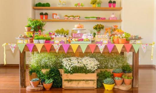 Decoração de Festa Jardim encantado com bandeirinhas e caixotes de feira.