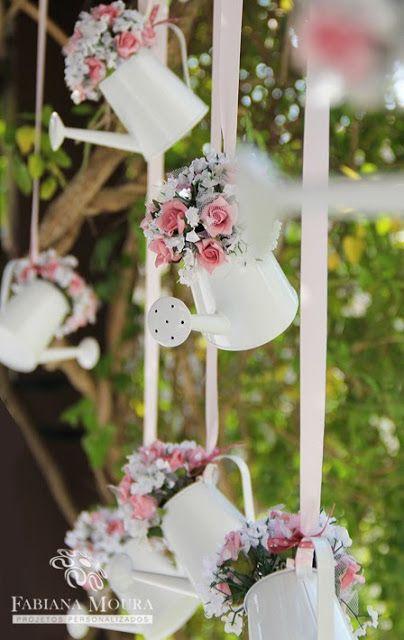 Pequenos regadores brancos com flores dentro, pendurados.