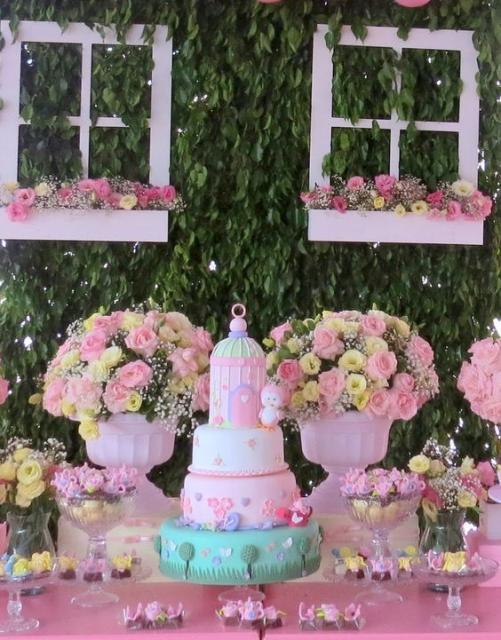 Janelas brancas e flores rosas usadas na decoração.