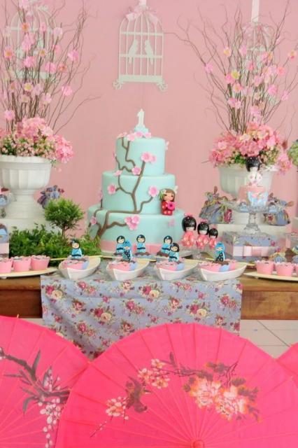 Vasos grandes brancos com flores rosa compondo a decoração da mesa.
