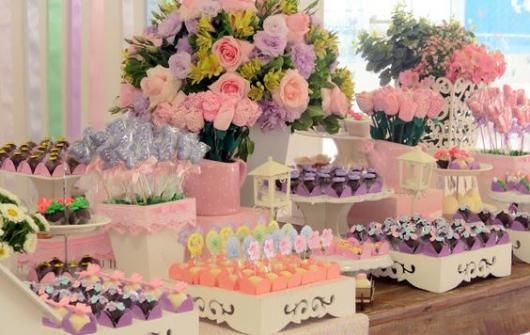 Mesa com docinhos, vasos e flores.