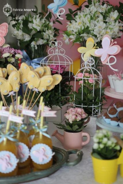 Mini gaiolas, xícaras, flores e borboletas na decoração da mesa.