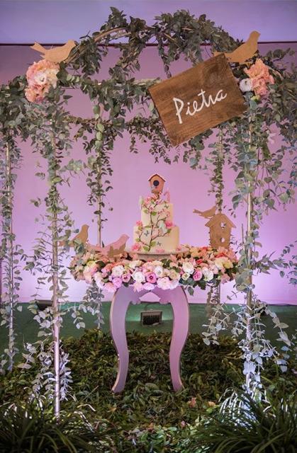 Mesa do bolo cheia de flores.