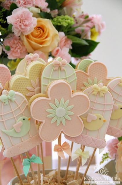 Pirulitos com decoração de flores e gaiolas com passarinhos.