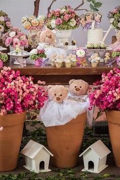 Vasos de barro na decoração, com flores e ursinhos dentro.