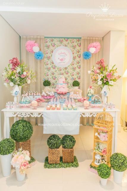Decoração de Festa Jardim Encantado com mesa branca e flores.