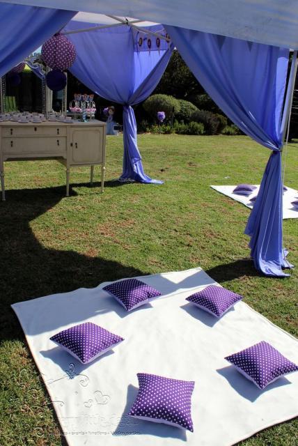 Móvel provençal com lembrancinhas sob tenda de tecido leve e azul no gramado. Tecidos brancos com almofadas em roxo espalhados pelo gramado.