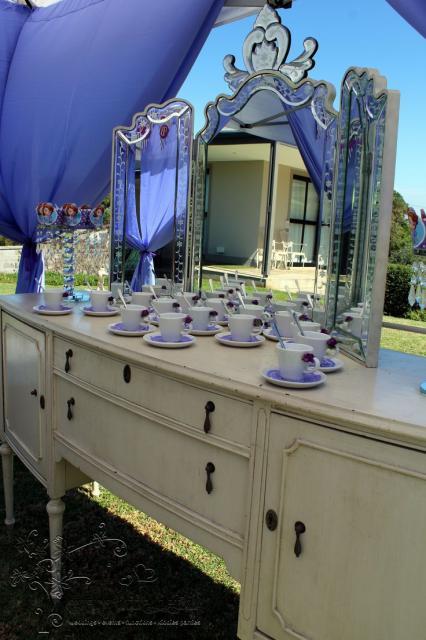 Detalhe de penteadeira com espelho adornado sob tenda. Xícaras feitas para lembrancinha das crianças ficam sobre a penteadeira.