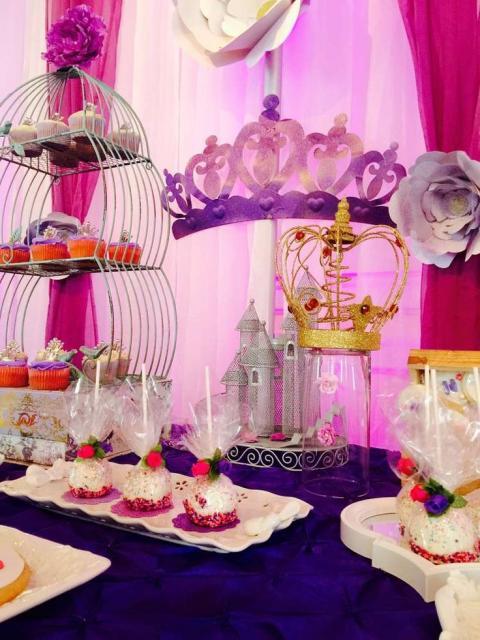 Decoração de festa princesa Sofia em cores variadas: mesa azul, detalhes rosa e roxo e fundo em dois tons de rosa.