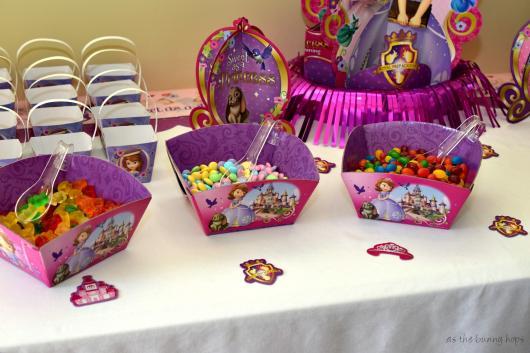 Mesa decorada com recipientes da festa princesa sofia com doces coloridos