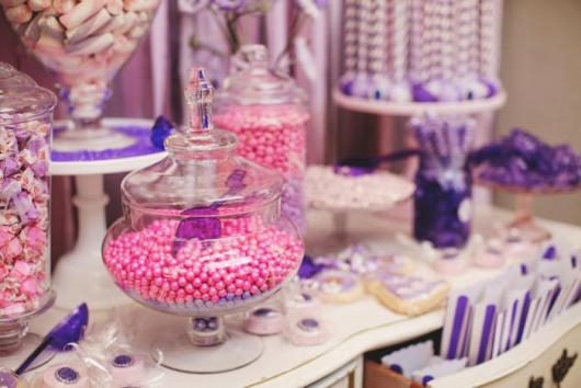 Mesa decorada com bombonieres preenchidas com doces cor-de-rosa